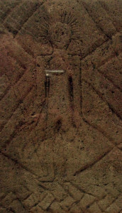 Figure carved on the Frankish grave stele of Niederdollendorf (7th century), known as the earliest material witness of Christian presence in the German Rhineland; the figure is presumably a depiction of Christ as a heroic warrior wielding a lance, with a halo or crown of rays emanating from his head